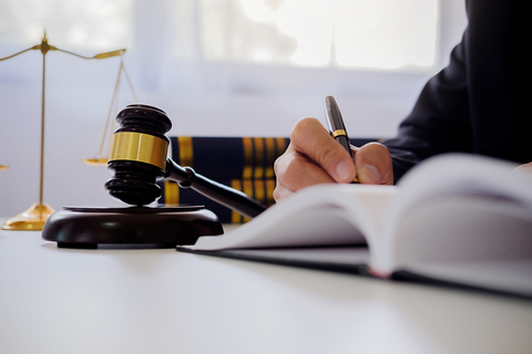 Lawyer seated at a desk and is writing in a book