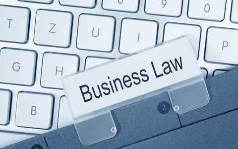 """Modern keyboard beneath a tabbed folder with text, """"Business law"""""""