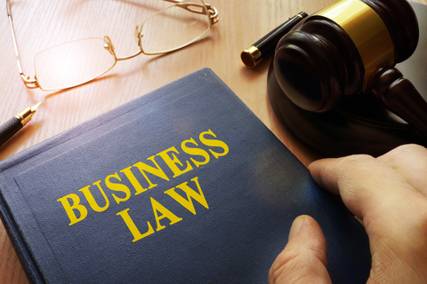 """Office desk with hand opening a book with text, """"Business law"""""""