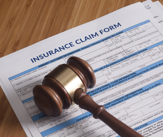 Gavel resting on top of an insurance claim form