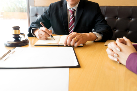 Legal office with a male lawyer writing on a pad of paper
