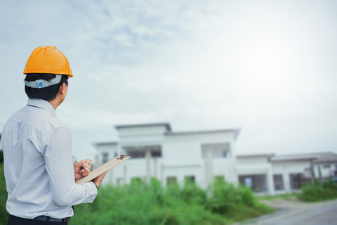 Male home inspector standing outside a home before an inspection
