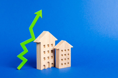 Two wooden blocks shaped like houses next to a green arrow
