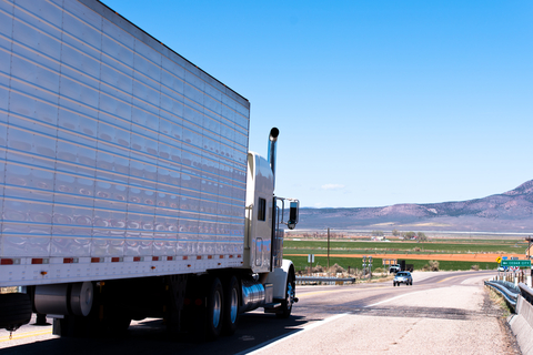 Semi truck with white trailer on an open road